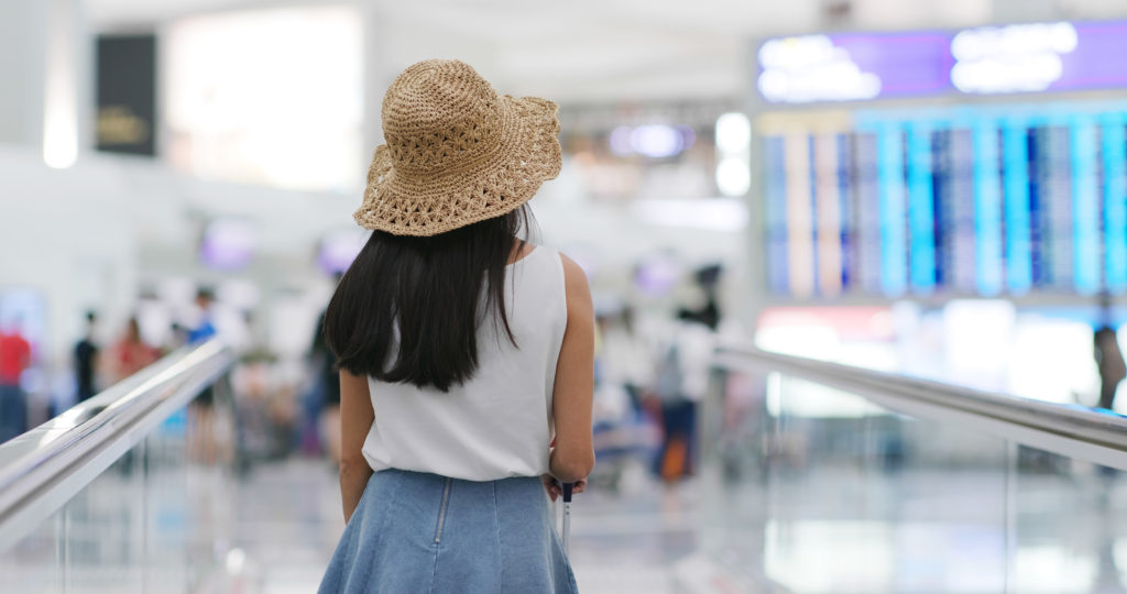 Woman go travel and look at the flight number in the airport